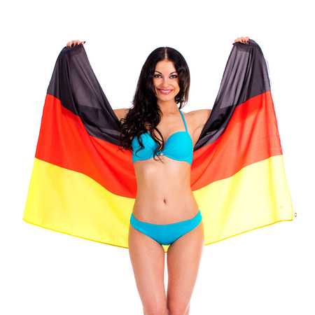 Young beautiful brunette woman in blue bikini holds up a clear flag of Germany