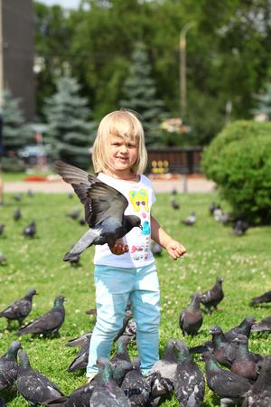 Happy little girl feeding doves, against green sunner park