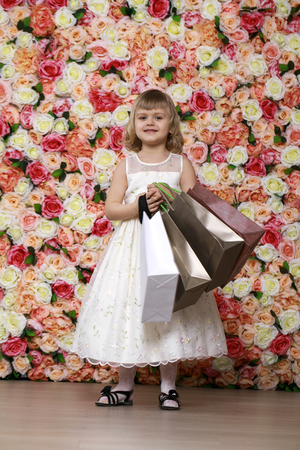 5s: Portrait of a beautiful blonde little girl in white gown with purchases in hands, background of a flower wall in the studio