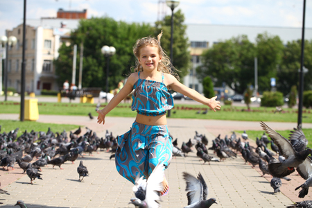 many babies: Young happy girl runs through a flock of pigeons on the square in summer city park