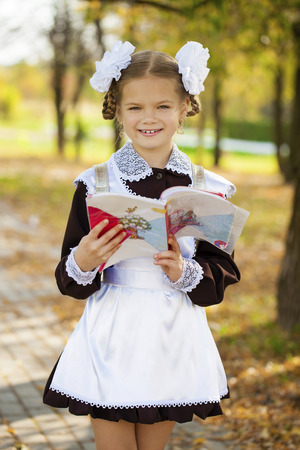 Portrait of a beautiful young first-grader in a festive school uniform on the background autumn park Stock Photo