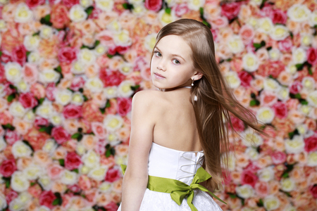 Portrait of a beautiful blonde little girl in white gown on a background of a flower wall in the studi