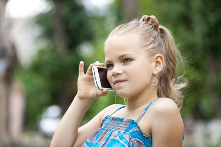 Close up, Little girl talking on cell phone against green of Park in summer Stock Photo