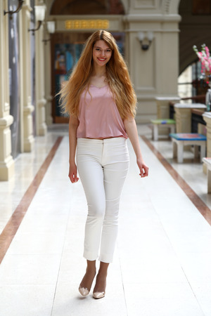 go inside: Full length portrait, young beautiful blonde woman in white pants and pink blouse walking in the shop