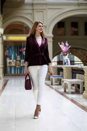 Full-length portret, jonge mooie blonde vrouw in witte broek en corduroy jas staat in de etalage Stockfoto - 81077419