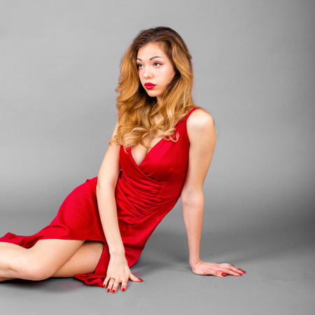 Beautiful young blonde woman in red dress on gray wall studio background Stock Photo