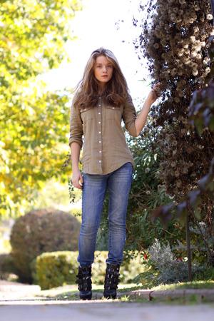 Jonge blonde vrouw in blauwe spijkerbroek in herfstpark