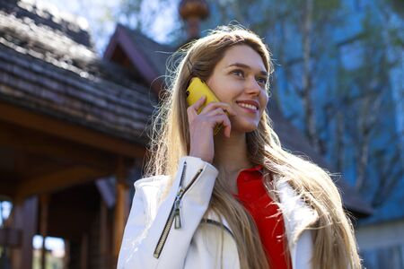 house call: Beautiful young blonde woman calling by phone, spring outdoors Stock Photo