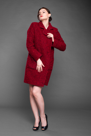 Portrait in full growth of a beautiful young woman in red autumn coat, isolated on gray background