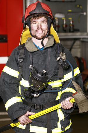 resistant: Close-up portrait of a young fireman on the background of a fire truck