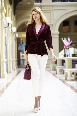 Full-length portrait, young beautiful blonde woman in white pants and corduroy jacket walking in the shop Stock Photo