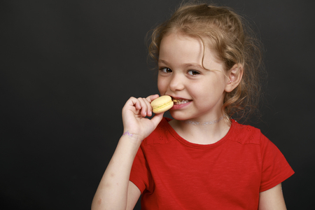 children party: Little blonde girl with freckles opened her mouth and wants to eat macaron yellow cake. Close-up, isolated on black background