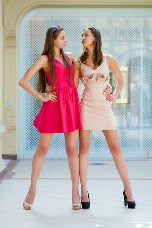 Two beautiful brunette women in summer dresses. Studio portrait Stock Photo