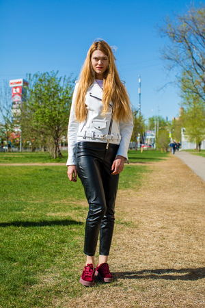 Slender young beautiful blonde girl in white leather jacket