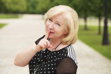Portrait beautiful woman with finger on lips, or secret gesture hand sign Stock Photo