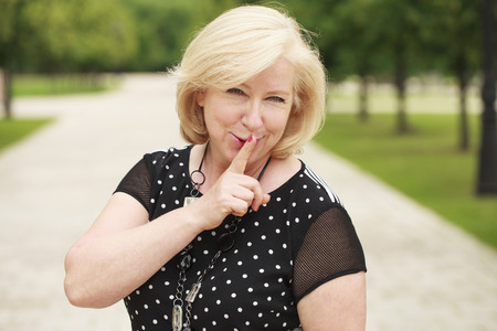 Portrait beautiful woman with finger on lips, or secret gesture hand sign Imagens