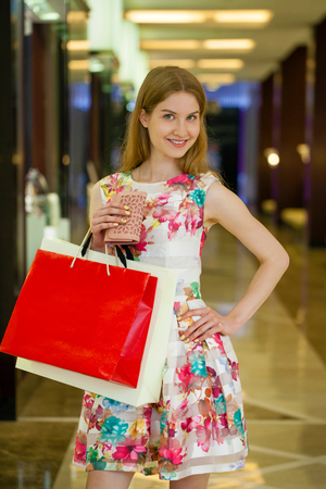 shopfront: Shopping. Young beautiful blonde woman with some shopping bags in the mall