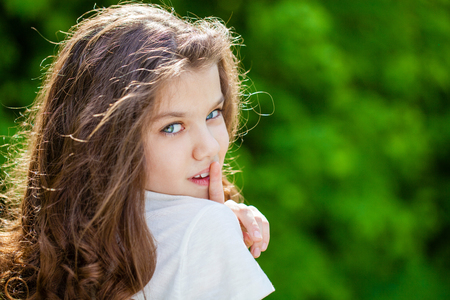 Young beautiful Little girl has put forefinger to lips as sign of silence, outdoors summer Stock Photo