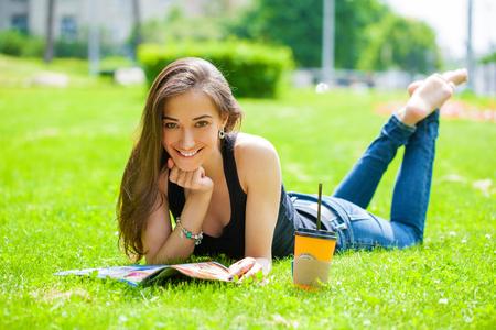 Jonge mooie bruine haired vrouw in blauwe spijkerbroek zittend op groen gras