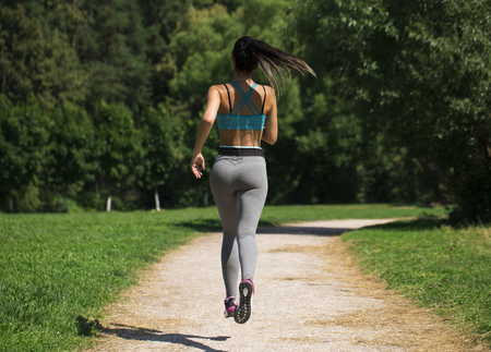 Athletic happy brunette woman working out in a meadow, from a complete series of photos Stock Photo