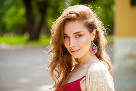 Portrait close up of young beautiful happy woman шт red dress, summer outdoors