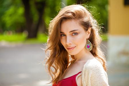 Retrato de cerca de joven hermosa mujer feliz ÑÑ, vestido rojo, verano al aire libre Foto de archivo