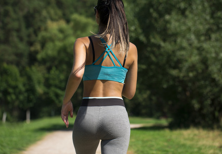 Close up sexy ass. Athletic woman working out in a meadow, from a complete series of photos
