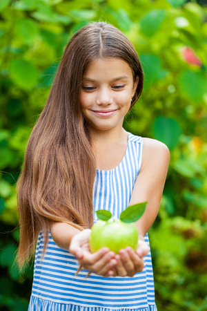 Happy brunette little girl with green apple, summer outdoors