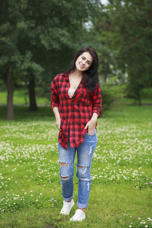 Full length portrait of a young beautiful woman in a crocheted red shirt and golly-torn jeans posing against a summer park