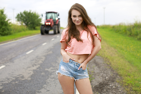 Portrait of a young beautiful girl in jeans shorts on a rural road Stok Fotoğraf