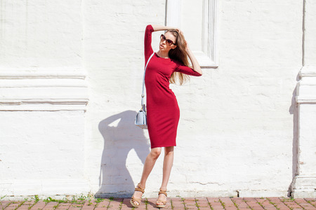 Portrait in full growth, Beautiful young brunette woman in red dress, against white wall, summer outdoors Stock Photo