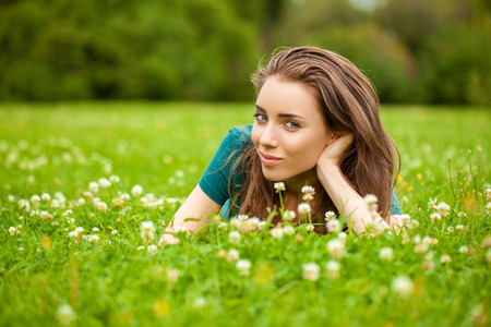 Young beautiful brown haired woman in blue jeans sitting on green grass