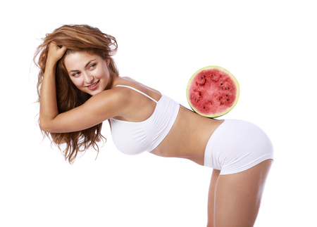 Fitness diet, Slice of watermelon. Young beautiful blonde woman in white fitness clothing, isolated on white background Imagens - 84255799