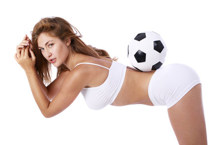 Sexy model and soccer ball. Young beautiful blonde woman in white fitness clothing, on white isolated background Imagens