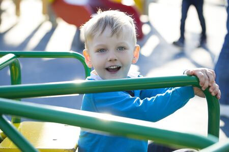 Portrait of a young blonde boy sitting on a carousel at the playground Stock Photo