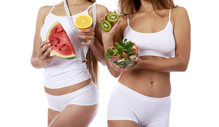 Fruits and vegetables for a diet. Dietary food in the hands of two slender models in sports white lingerie, isolated on white background Stock Photo
