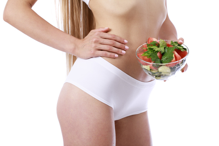 Dietary salad and slender female figure in sports white lingerie, isolated over white background
