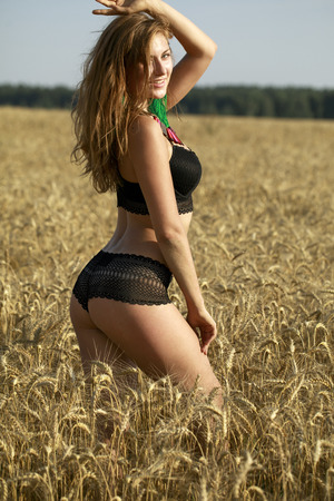 Young beautiful blonde woman in black dancers suit in wheat field Stock Photo - 86146313