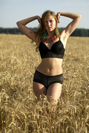 Young beautiful blonde woman in black dancers suit in wheat field Stock Photo - 86146322