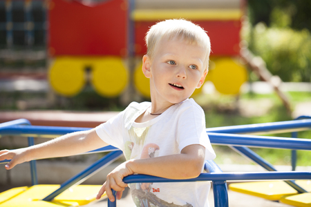 Portrait of a young blonde boy sitting on a carousel at the playground Stok Fotoğraf