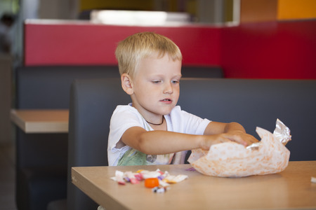 Portrait of a young blonde boy in cafe, indoor