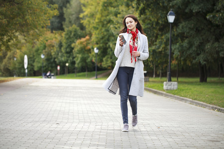 Beautiful young brunette woman calling by phone in autumn park