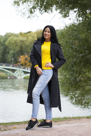 Young brunette woman in gray woolen coat on background autumn park