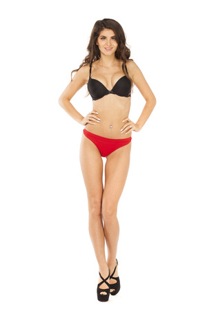 Portrait of young brunette woman in black bra and red underpants, isolated on white background Stock Photo
