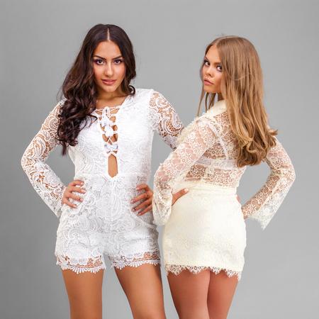 Dos mujeres sexy en vestido sexy blanco, aislado en fondo gris Foto de archivo - 87738341