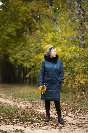 Portrait of a gray-haired elderly woman in an autumn park Stock Photo