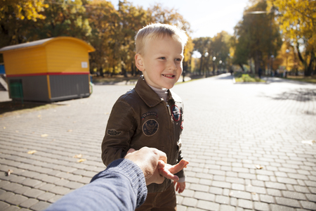 Follow me, Beautiful little boy holds the hand of a father in autumn city park Stock Photo