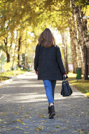 Back view. Portrait of a full length brunette woman in a gray woolen coat walking in autumn park