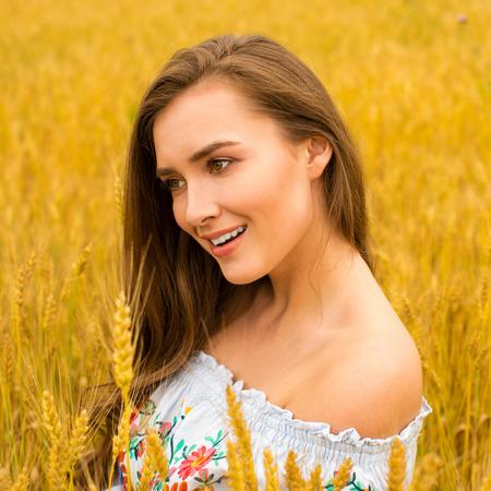 Ritratto di una giovane donna bruna su uno sfondo di campo di grano dorato, estate all'aperto Archivio Fotografico - 89395850