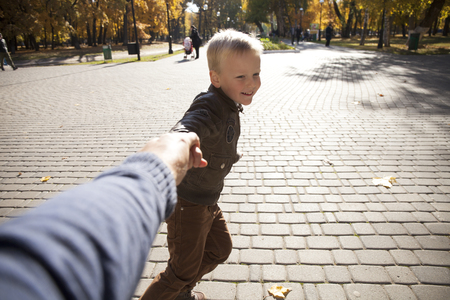 5s: Follow me, Beautiful little boy holds the hand of a father in autumn city park Stock Photo